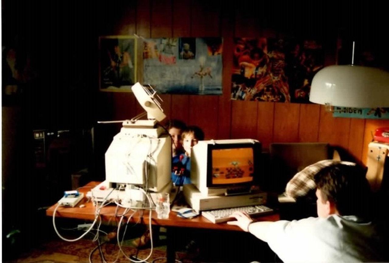 """Mein Amiga ist der linke im Bild. Der rechts gehört Dirk, der später das Netzwerk Café eröffnen sollte. Mit ihm habe ich Anfang der 80er endlose Runden Artillery Duel gespielt. Die Nachbarsjungen im Hintergrund, Georg und Gunnar, waren oft bei uns und haben sich am Amiga die Zeit vertrieben. Keine Ahnung was die da eigentlich gespielt haben. Vorn im Bild ist Nicolas zu sehen. Das Bild wurde Anfang 1990 aufgenommen. In diesem Jahr sollte ich noch mit Nicolas einen Fußballmanager in genau diesem Zimmer an genau diesem Tisch und auf genau diesem Amiga 1000 (links im Bild) spielen. Nicht einfach nur spielen! Mein Bruder Thomas würde sagen: """"... das haben Du und Nicolas wie die Bekloppten den ganzen Sommer durch bei schönstem Wetter gespielt"""". (Bild: Michael Müller)"""